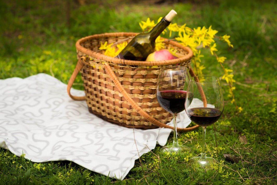 Weintasche für ein Picknick auf einer Wiese mit Korb