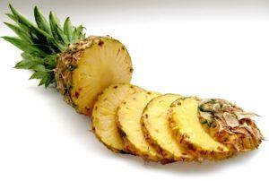 ananas geschnitten mithilfe eines ananasschneiders