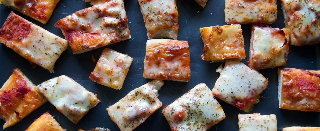 Kleine und geschnitte Pizza mithilfe einer Pizzaschere
