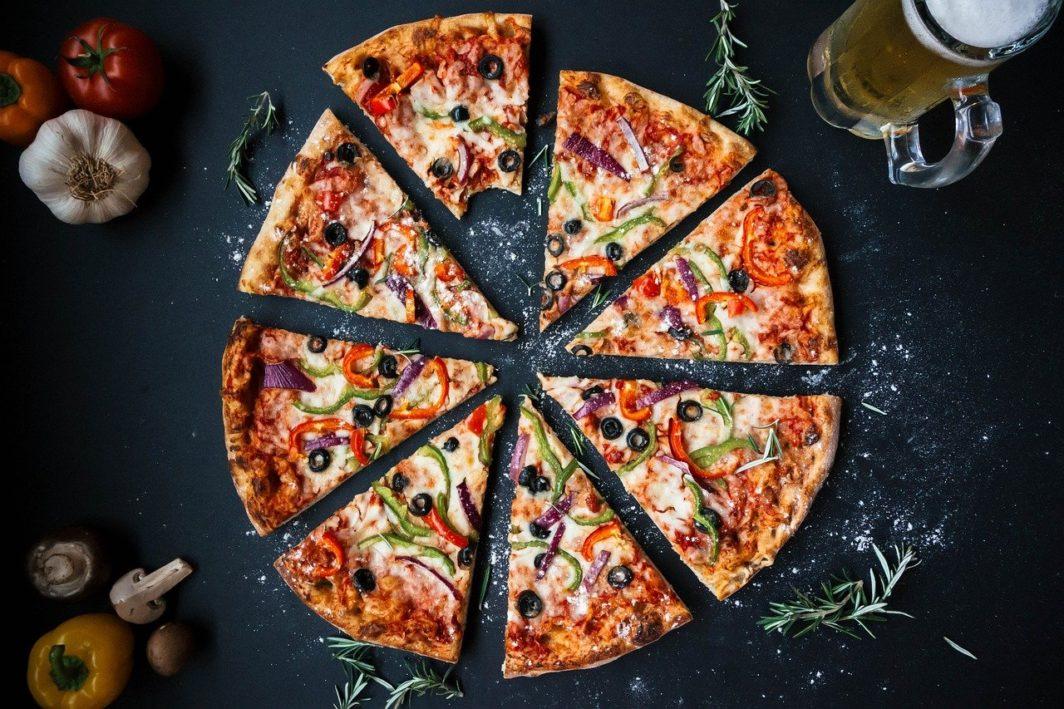 Geschnitte Pizza mithilfe einer Pizzaschere